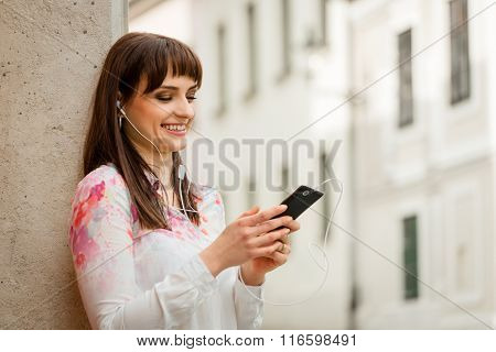Woman listening music on phone in street