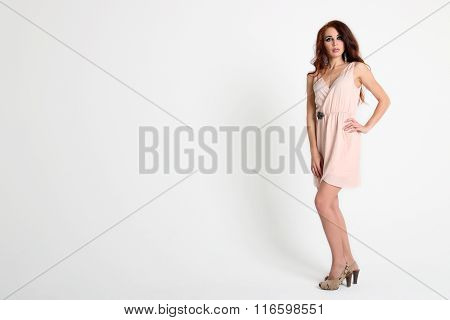 Standing Beautiful Young Girl With Red Hair With Short Beige Dress And Shoes With Heels