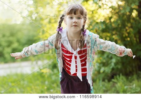 Pretty Smiling Little Girl With Braids Depicts Bird At Summer Sunny Day