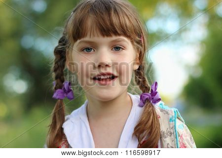 Close Up Portrait Of Pretty Smiling Little Girl With Braids Outdoor. Shallow Dof