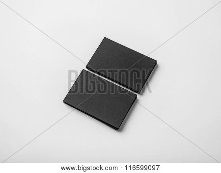 Two stack of blank black business cards on white background with soft shadows.