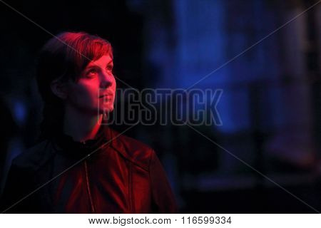Beautiful Woman In Leather Jacket Looks Away In Red Light At Night On Street