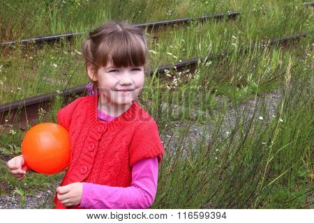 Pretty Little Girl With Ball Stands Near Old Railway Among Grass At Summer