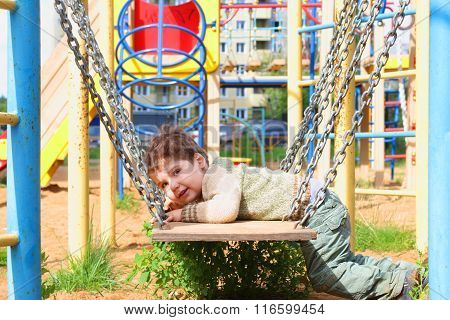 Handsome Little Boy Lies In Swings With Chains On Playground At Summer Day