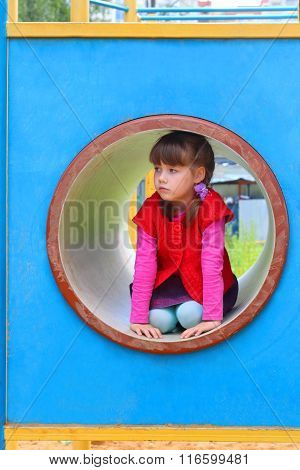 Pretty Little Girl Lies In Pipe On Playground At Summer Day And Sad