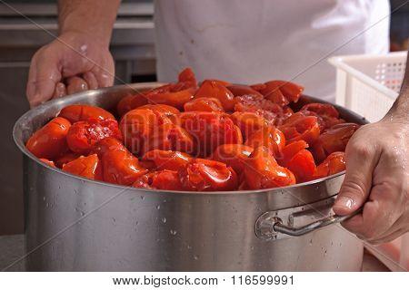 Cook hands squeezing tomato preparing passata sauce.