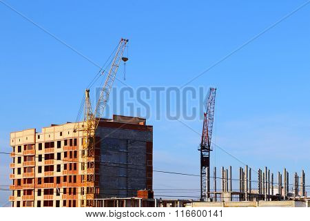 Part Of Tall Cranes And Building Under Construction At Sunny Winter Day