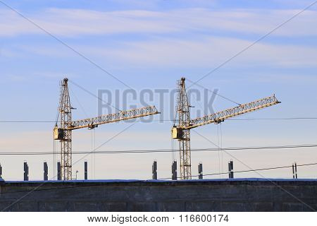 Two Stationary Hoists Androof Of  Building And Wires At Winter Day With Cloudy Sky