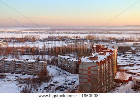 Frozen River, Roof Of Tall Building In Snow And Sky At Cold Winter Evening