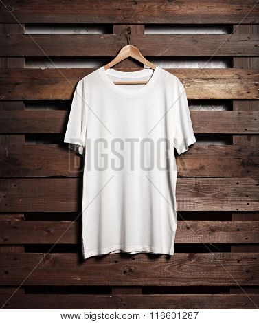 Photo of white tshirt hanging on wood background