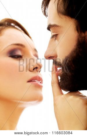 Woman putting her finger on man's lips