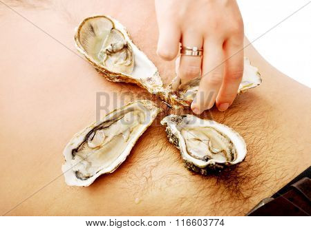 Woman putting oysters on man's belly.