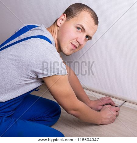 Young Worker Installing New Skirting Board At Home