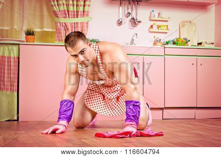 Handsome muscular man in an apron mopping the floor in the pink kitchen. Love concept. Valentine's day.