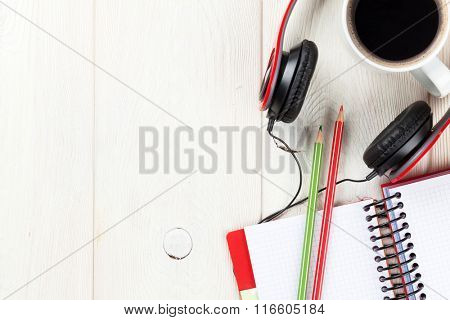 Office wooden desk with notepad, coffee cup and headphones. Top view with copy space