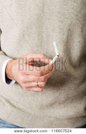Male hand with broken cigarette