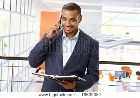 Smiling, happy, afro american office worker at business center with mobile phone and personal organizer. Looking at camera, copyspace.