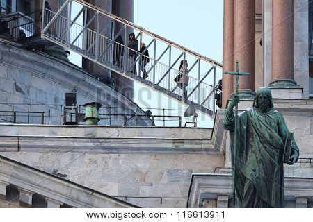 ST. PETERSBURG, RUSSIA - JANUARY 5, 2016: Tourists ascending to the colonnade of St. Isaac's cathedral. Sculpture of apostle Philip created by Giovanni Vitali is visible on the front