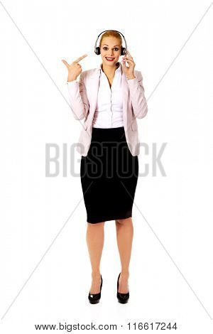 Happy female phone operator pointing at headphones