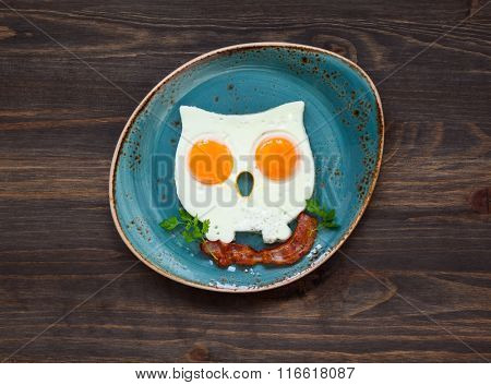 owl-shaped fried eggs with crispy bacon on a  plate
