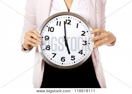 Young business woman holding office clock