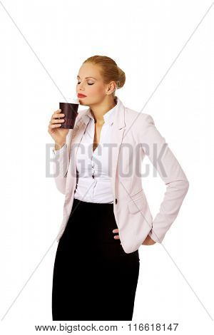 Business woman smelling coffee in paper cup