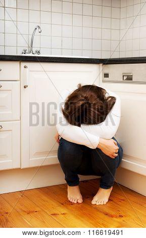 Woman sitting on kitchen floor in depression.