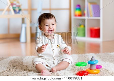 cute cheerful baby playing with colorful toy at home
