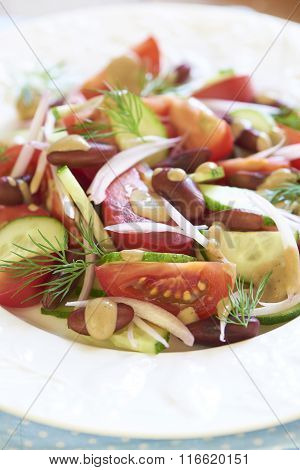 Salad with tomatoes, cucumbers, onion, beans and tuna sauce