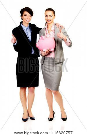 Two businesswoman with piggy bank.