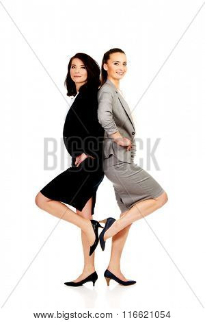 Two businesswoman leaning on each other.