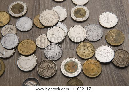 Assorted currency coins from UAE, India, Kuwait and Egypt.