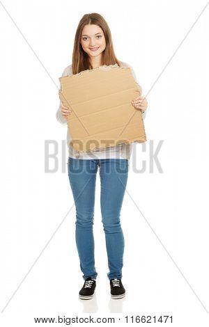 Teen woman holding cardboard sheet.