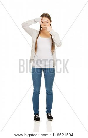 Teen woman with frame gesture.