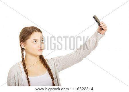 Teen woman taking selfies with smart phone.