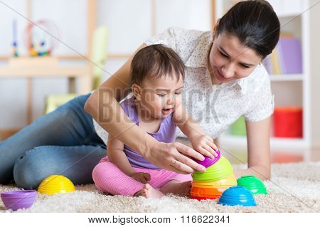 mom and kid playing block toys at home