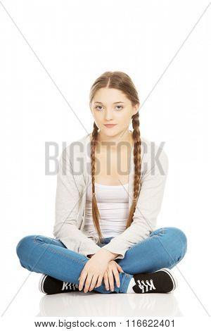 Happy teen woman sitting cross legged.