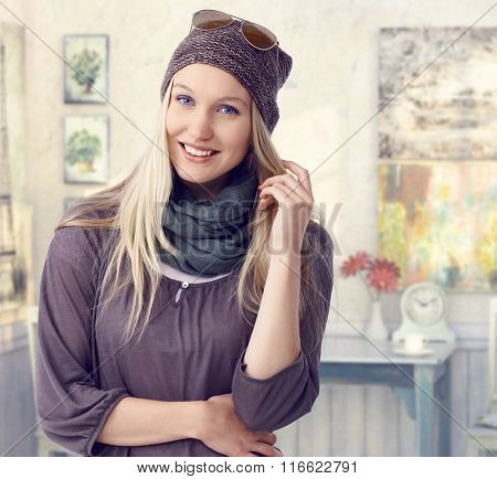 Happy young casual caucasian blonde visual artist woman at retro room. Standing, smiling, looking at camera.