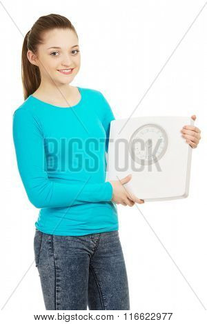 Beautiful teenager holding a scale.