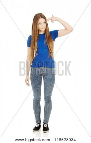Despair teenage woman making gun sign.
