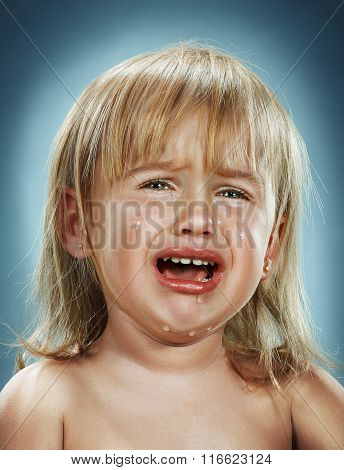 Portrait of a little girl. She is crying