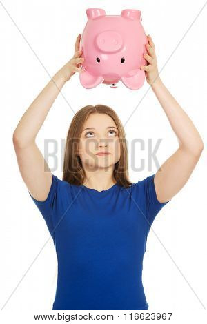 Teenage woman shaking piggybank.