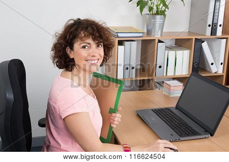 Smiling Adult Office Woman Sitting At Her Desk While Holding A Folder  And Looking At The Camera.