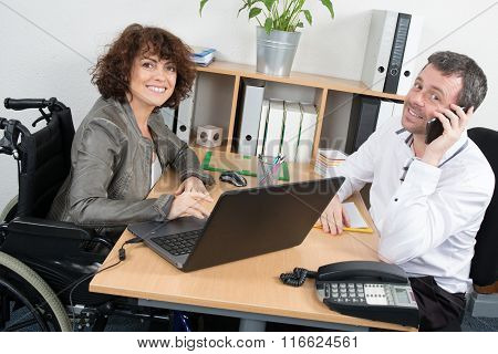 Casual Woman In Wheelchair Working At Her Desk With Colleague