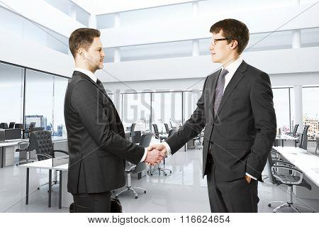 Businessmen Shake Hands In Modern Open Space Office
