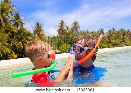 happy father and son snorkeling on beach