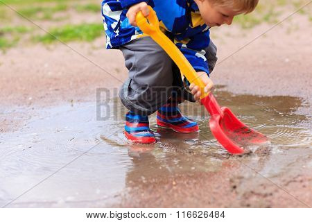 child playing in water puddle, kids spring activities