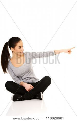 Woman sitting cross legged pointing aside.