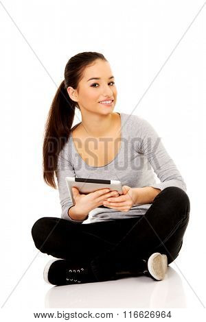 Woman with tablet sitting cross legged.