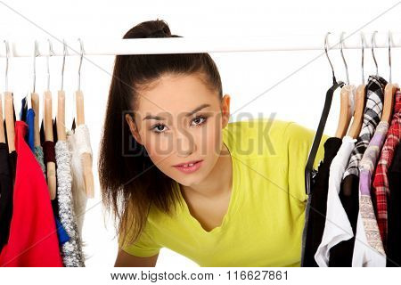 Young woman with clothes on hanger.